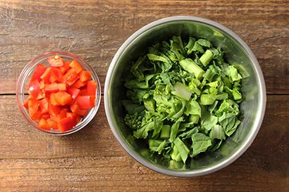 菜の花は汚れていれば軸を少し切り、1cm幅に切る。へたとわたを取った赤パプリカは1cm幅の角切りにする。