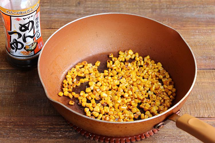 炊いている間にフライパンにごま油をひき、とうもろこしの実を入れ、中火〜強火で全体に焼き色がつくまで炒める。めんつゆ(分量外:小さじ2)を入れ、手早く炒めたら火を止める(とうもろこしははねやすいので蓋をうまく使いながら)。