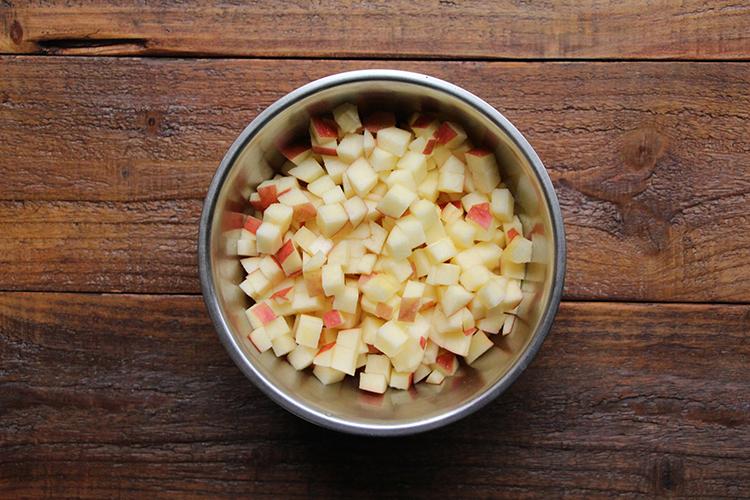 りんごは皮付きのまま縦半分にカットし、芯を切り取り、5mm幅の角切りにする。