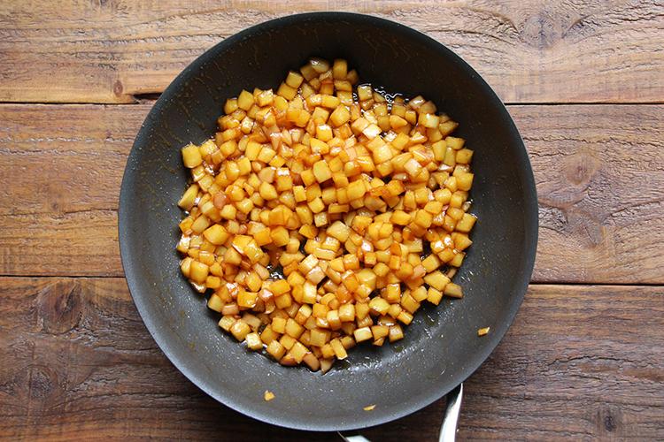 フライパンに【A】を入れ、中火前後で火にかける。時々揺すり、茶色くなってきたら火を止め、割烹白だしをヘラに伝わらせるように流し入れる。りんごを加え、再び中火前後で火にかけ、りんご全体が色づきとろみが出るまで6〜8分煮炒め、火を止める。