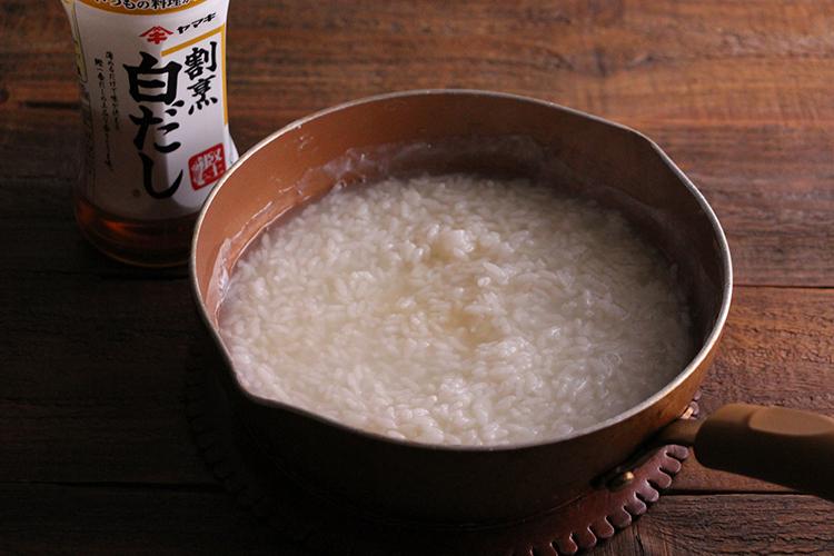 フライパンに割烹白だし、水、米を入れ、ひと煮立ちさせる。時々混ぜ合わせながら弱火で10分ほど煮る。(煮上がる少し前に餅をオーブントースターで加熱する。)