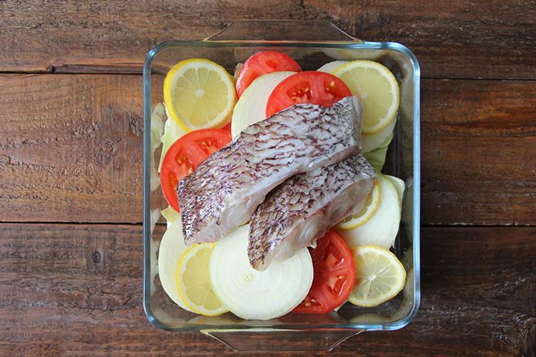 キャベツ、新玉ねぎ、絞ったレモン、トマト、真鯛をバランスよく盛り付ける。ふんわりとラップをかけ、電子レンジで6〜8分ほど加熱する。粗挽き黒こしょうをかけ、オリーブオイル(分量外:少々)をかける。