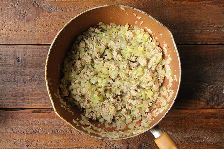 《ミートソースを作る①》 温めたフライパンにオリーブオイルをひき、鶏ももひき肉を入れ、中火前後で肉の色が変わるまで炒める。玉ねぎ、セロリを加え、さらに5分ほど炒める。