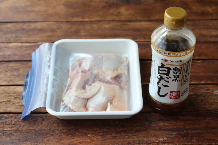 鶏もも肉は厚い部分に浅く切り込みを入れて半分に切る。保存用袋などに鶏もも肉と割烹白だしを入れて全体になじませ、空気を抜いて密閉する。冷蔵庫で30分~1時間おく。レモンは2枚薄切りにし、残りは果汁を絞る。