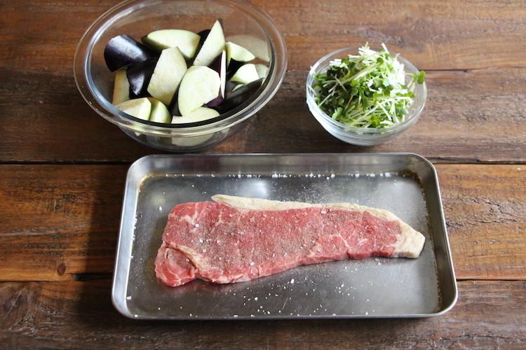 牛肉ステーキ用は焼く20〜30分前に常温に戻し、焼く直前に塩、粗挽き黒こしょうをふる。ナスはヘタを切り落とし、1cm弱の輪切りにする。かいわれ大根は根元を切り落とし、2〜3cm幅に切る。大根はすりおろし、さっと水気を切る。