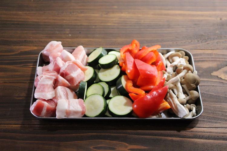 豚肉は1cm弱の厚さに切る。ズッキーニは1cm弱の厚さに切り、へたとわたを切り落としたパプリカは乱切りにし、しめじは石づきを切り落とす。