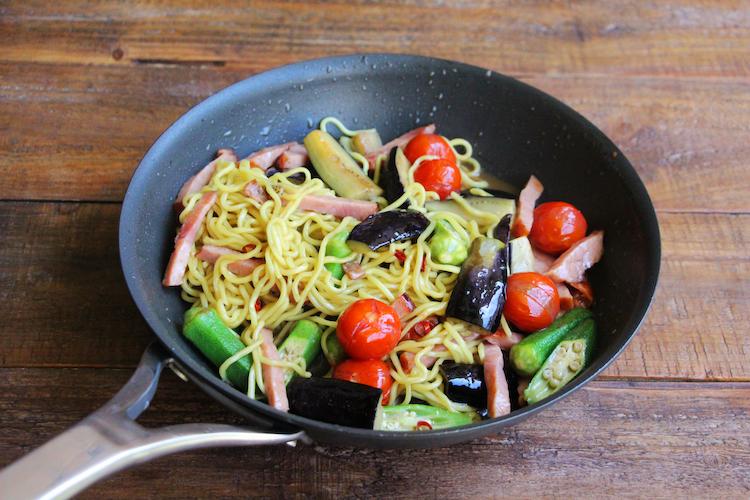 焼き豚、オクラ、ミニトマトを入れ、中火〜強火で1分ほど炒める。中華麺、2を入れ、ほぐしながら同様の火加減で1〜2分炒めたら器に盛り付ける。かつお節 、青ねぎをのせ、ごま(分量外:少々)をふる。