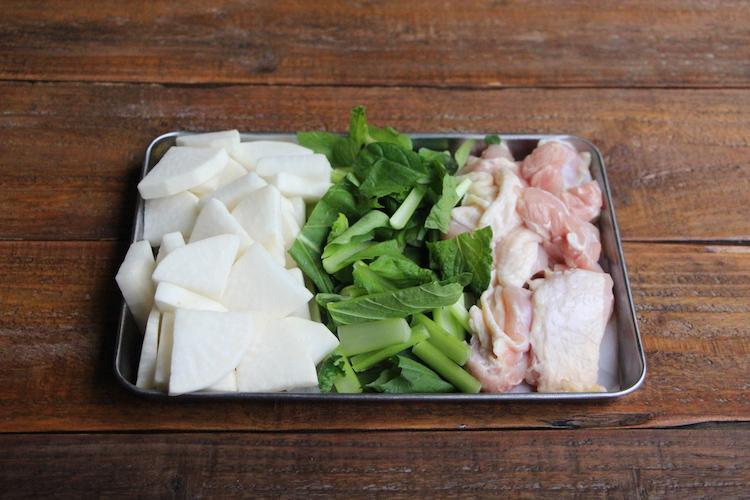 鶏肉は皮をつけたままぶつ切りにし、大根は皮をむき、5〜7mm幅のいちょう切りにする。茎を切り落とした小松菜は5cm幅に切る。