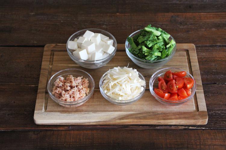 ツナ缶は水分を切り、豆腐はキッチンペーパーで包んで軽く水気を切り1cm幅の角切りにする。菜の花は2cm幅に切り、えのきだけは2cm幅に切る。ミニトマトはへたを取り、縦に十字に切って4等分にする。
