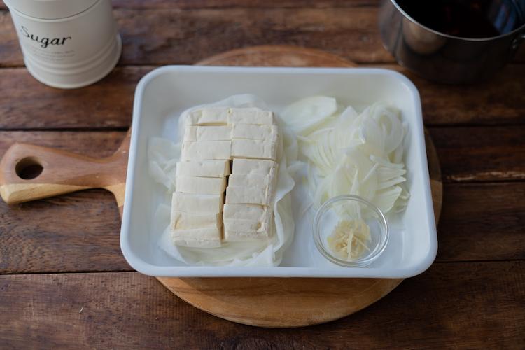 玉ねぎは薄切り、しょうがはせん切り、赤唐がらしは種を取って輪切りにする。豆腐は食べやすい大きさに切り、ペーパータオルで水分をしっかりとふく。