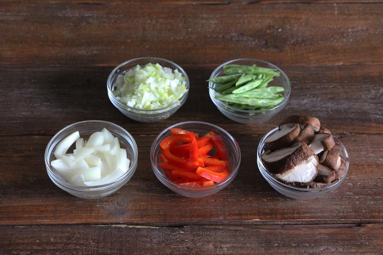 ~野菜の下ごしらえ~<br>さやいんげんはへたを切り落とし、2~3cm幅の斜め切りにする。しいたけは軸を切り落とし、1cm幅に切る。パプリカはへたと種を切り取り、5mm幅に切る。玉ねぎは横半分に切ってから5mm幅に切る。長ねぎは粗みじん切りにする。