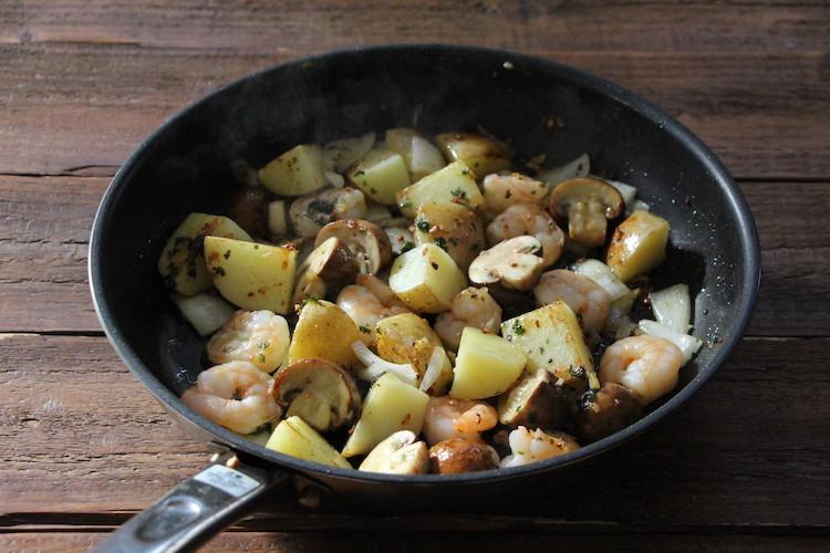 温めたフライパンにバター、にんにく、パセリを入れ、にんにくから香りが出るまで弱火で加熱する。えび、じゃがいも、マッシュルーム、玉ねぎを加え、中火前後で3~4分炒める。