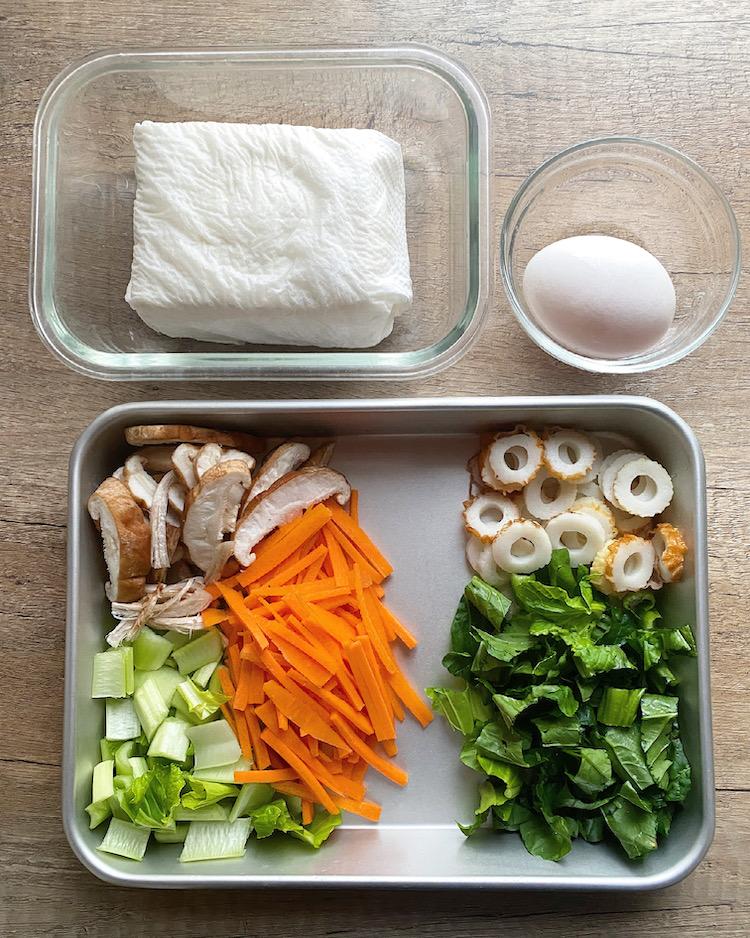 豆腐はペーパータオルに包んで耐熱容器に入れ、電子レンジ(500W)で3分加熱する。ペーパータオルを取り替えて重石をし、5~10分おいて水切りをする。にんじんは細切りにし、しいたけは石づきを切り落とし、かさは薄切り、軸は手で裂く。小松菜は1cm長さに切り、葉と茎に分けておく。ちくわは薄切りにし、卵は溶いておく。
